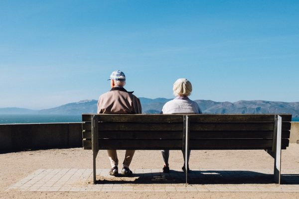 Two Older People on Bench viewing mountains